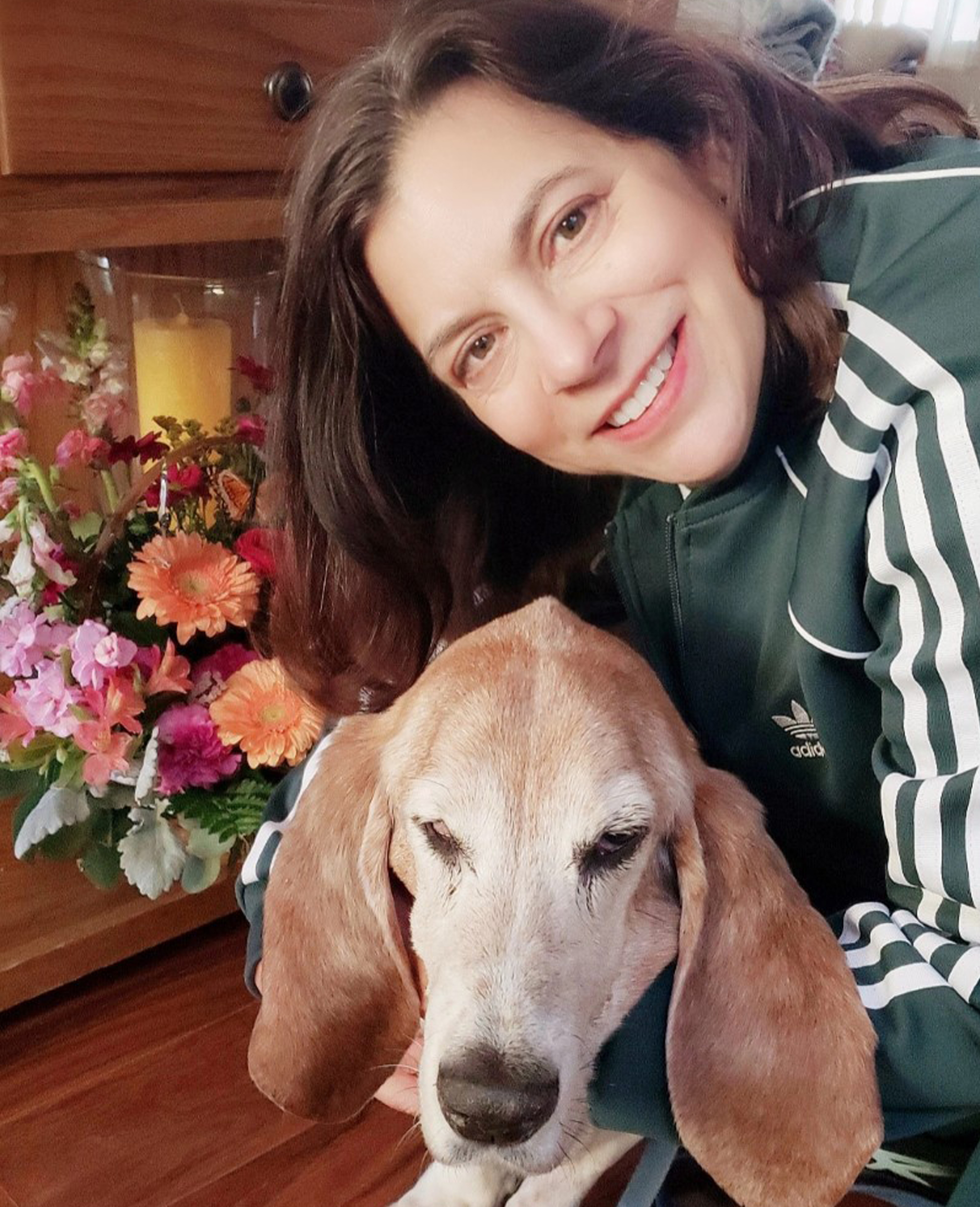 Dr. Laura Gonzales hugs a sweet bassett hound and smiles.