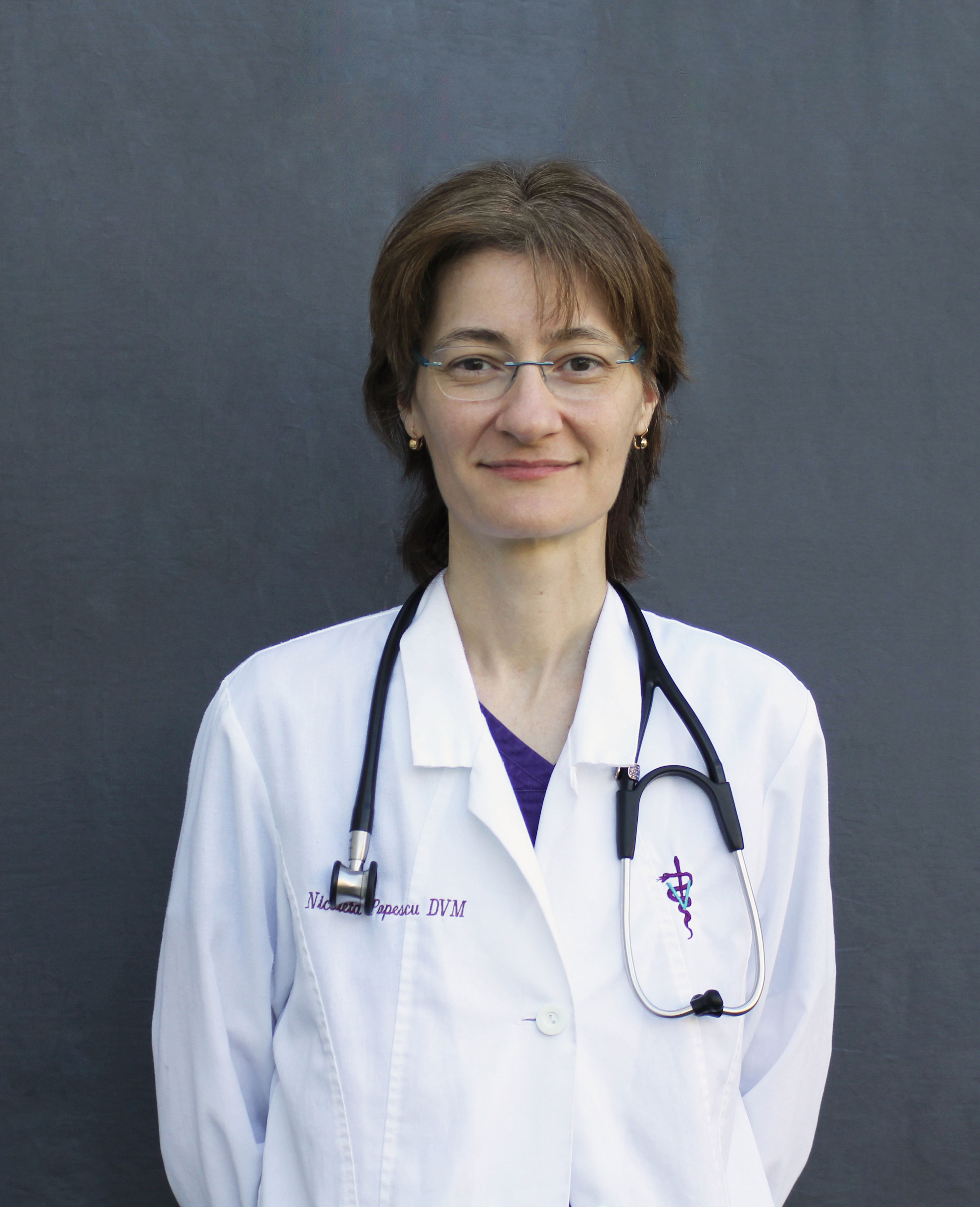 Dr. Nicoleta Popescu, a tall, slim female veterinarian in a white lab coat with a stethescope around her neck. She has short brown hair and wears glasses and purple scrubs.